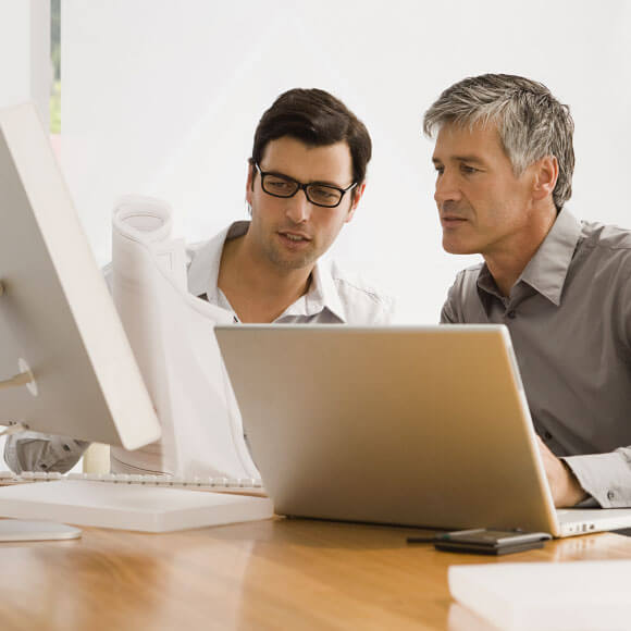 Image of Two persons looking over information in laptop